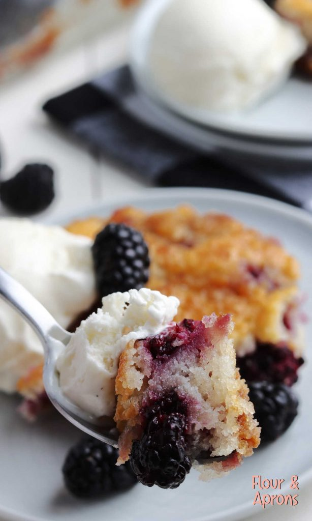 fork with blackberry cobbler and vanilla ice cream on it.