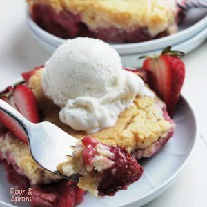 fork with a bite of strawberry cobbler on it, background has a plate with strawberry cobbler and ice cream.