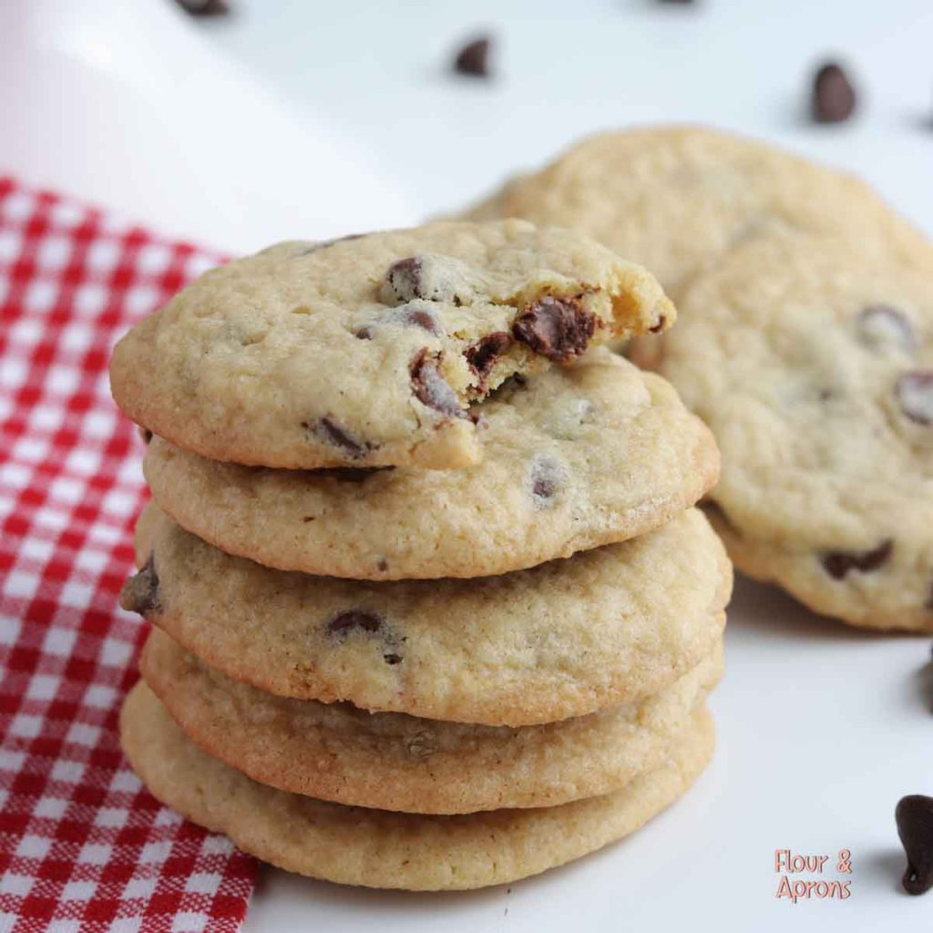 Stack of chocolate chip cookies with the top one having a bite taken out of it.