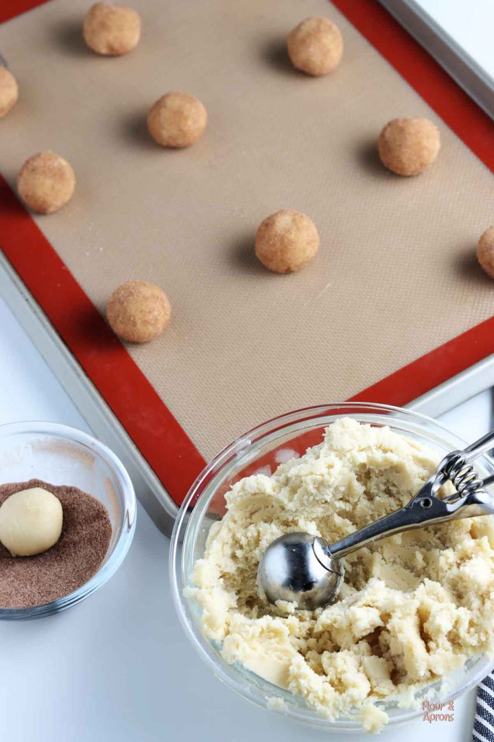Bowl of dough, ball of dough in small bowl of cinnamon and sugar and a cookie tray with balls of dough covered in cinnamon and sugar.